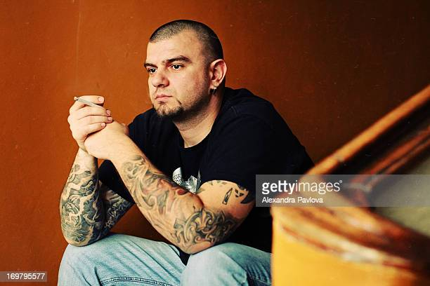 man with tattooed arms sitting and smoking