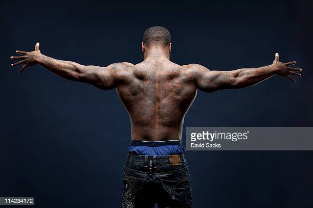 Man with tattoos, arms spread, back view