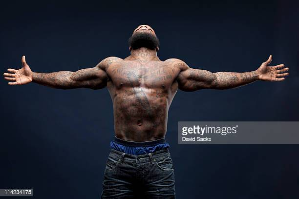 Man with tattoos, arms spread open
