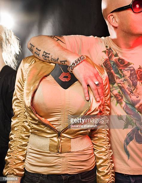 a man with tattoos holding a headless woman. - headless man stock pictures, royalty-free photos & images