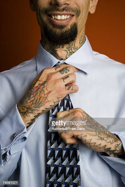 Man with tattoos in shirt and tie smiling