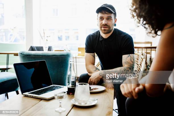 Man With Tattoos Talking Meeting With Colleagues For Lunch At Cafe