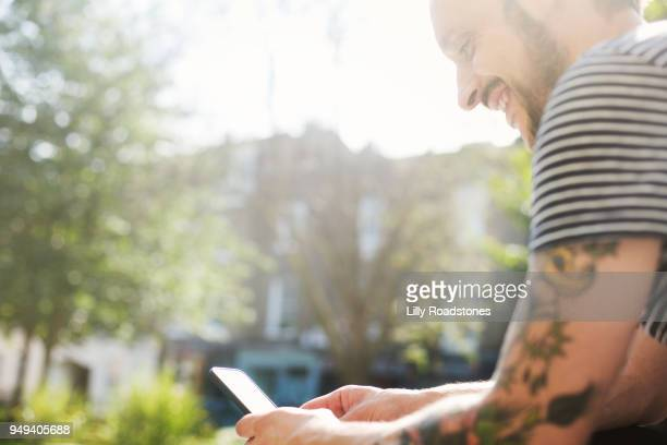 Man with tattoos using mobile phone