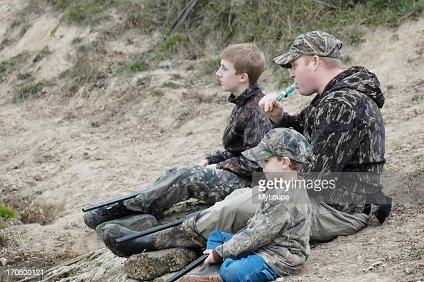 Man With Teenage Boy And Younger Boy Sitting At The Edge Of A Pond Calling Ducks And Waiting For Them To Fly In