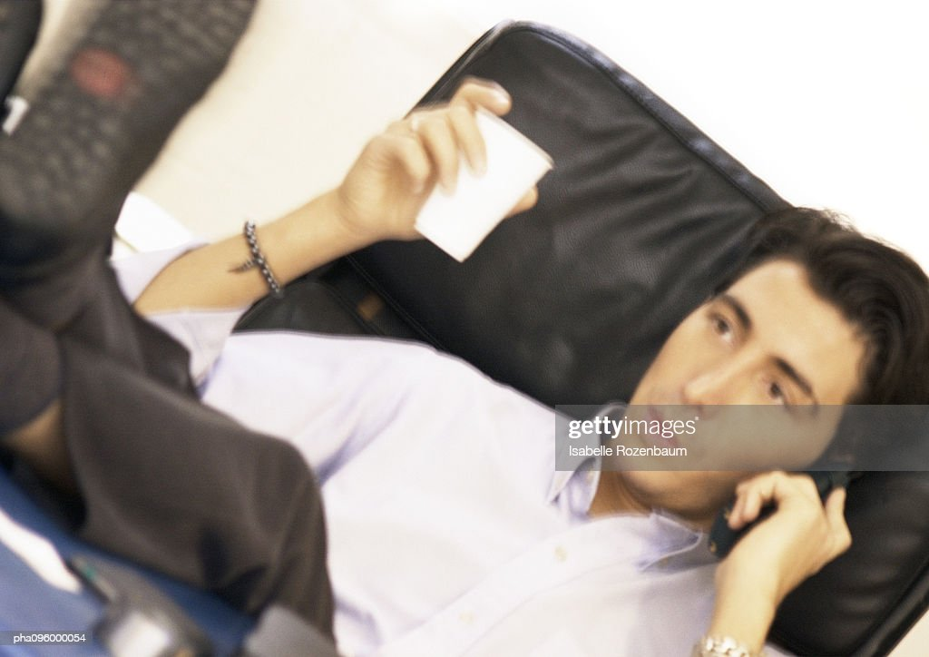 Man with telephone and plastic cup : Stockfoto