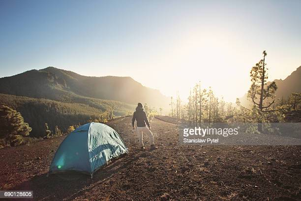 man with tent in mountains looking at sunrise - キャンプ 1人 ストックフォトと画像