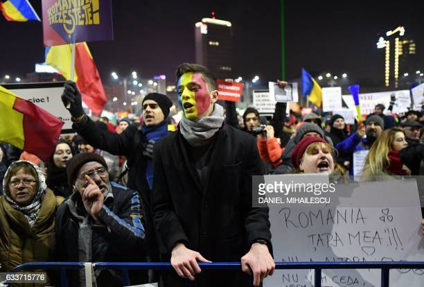 Man with the colours of the Romanian flag painted o his face, protests along with other people in front of the government headquarters in Bucharest,...