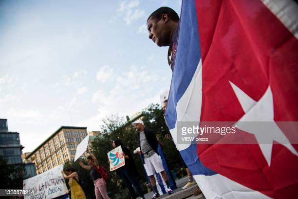 Man with the Cuban flag accompanies Cuban protesters in Union Square Park on July 14, 2021 in New York City. A small group of people gathered in...