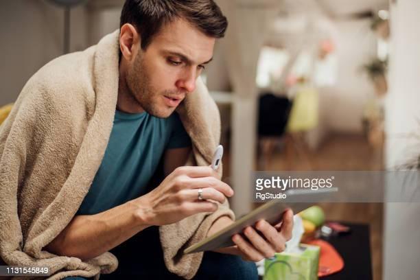 デジタルタブレットを使ったインフルエンザの男 - digital thermometer ストックフォトと画像