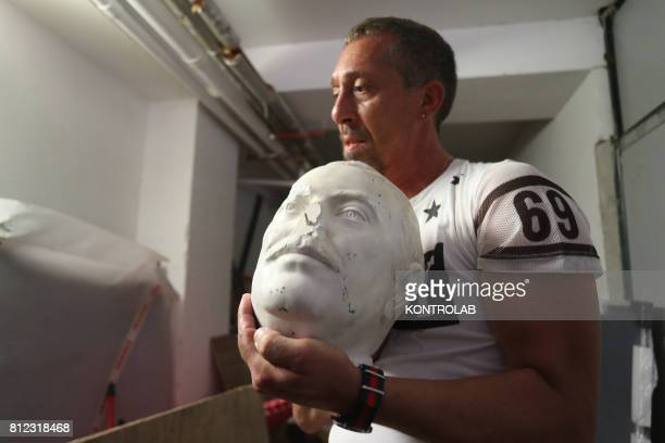 A man with the head of the statue of Giovanni Falcone destroyed by vandals in Palermo Sicily southern Italy in the Zen district
