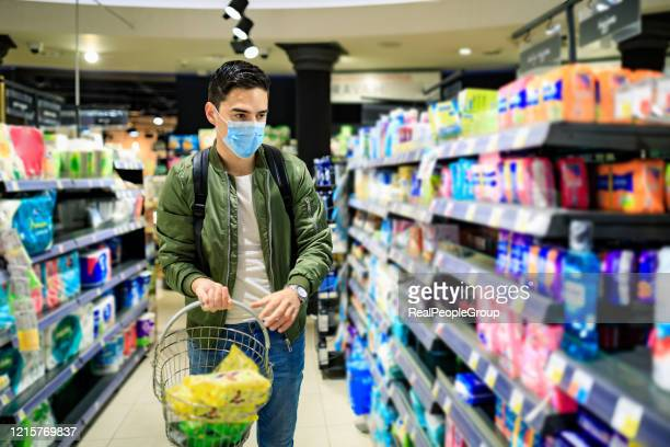 man with the mask on his face at the supermarket is looking for a disinfectant - man shopping stock pictures, royalty-free photos & images