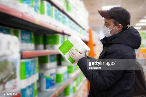 man with the mask on his face at the supermarket - buying toilet paper stock pictures, royalty-free photos & images
