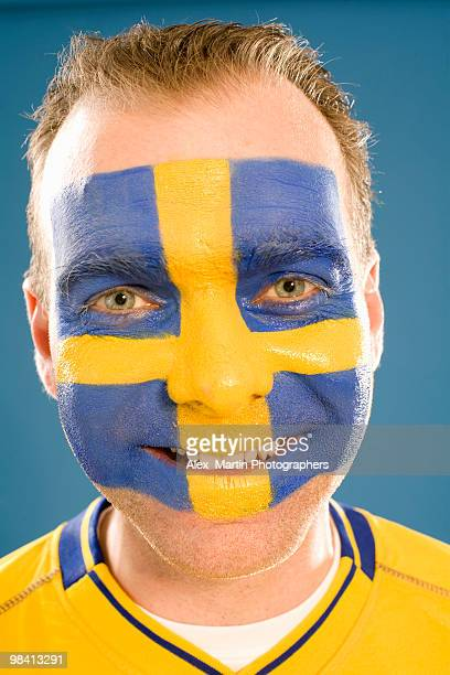 A man with the Swedish flag painted in his face.