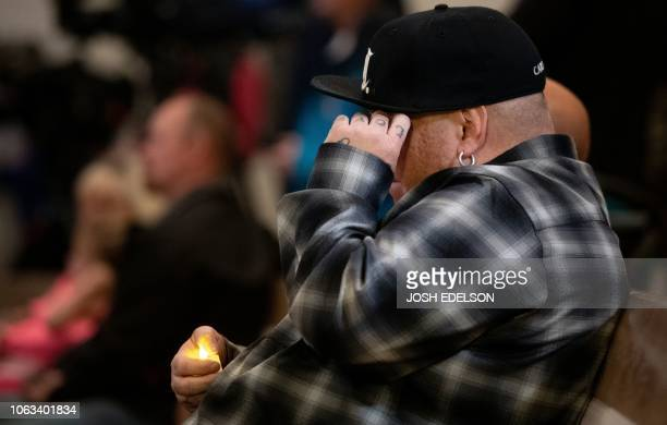 A man with the word 'love' tattooed on his hand cries during a vigil for victims of the Camp Fire at First Christian Church in Chico California on...