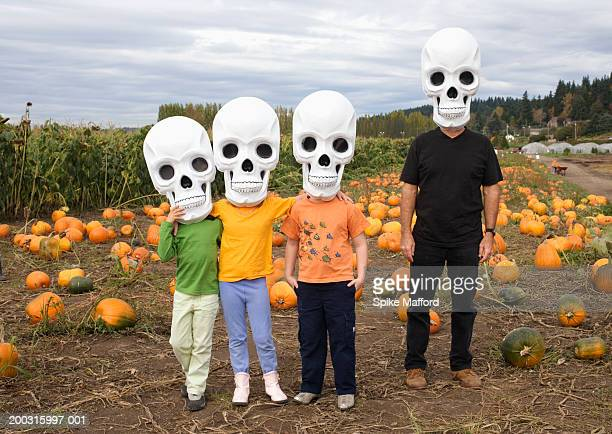man with three children (6-8)  in pumpkin patch, wearing skull masks - crazy dad stock photos and pictures