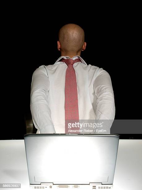 Man With Tie On His Back Using Laptop