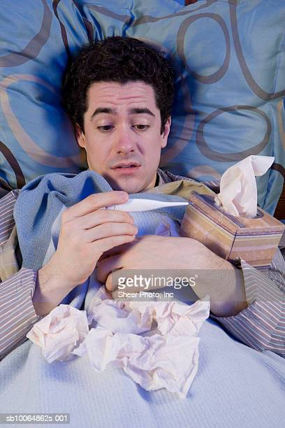 Man with tissues looking at thermometer in bed, elevated view