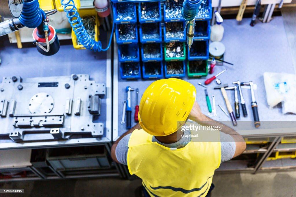 Mann mit Tools auf industriellen Werkbank : Stock-Foto