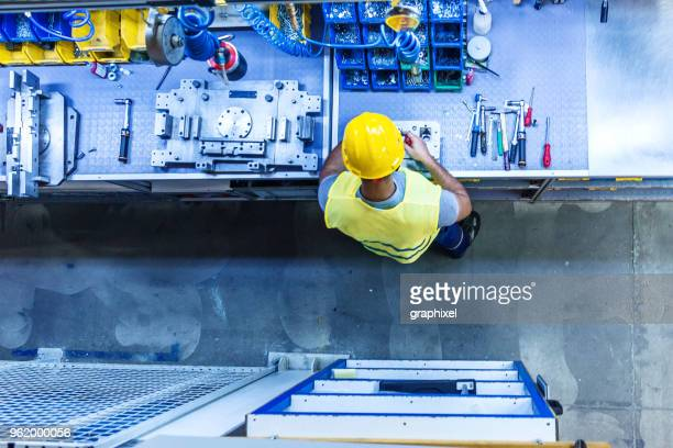 Man with Tools on Industrial Workbench