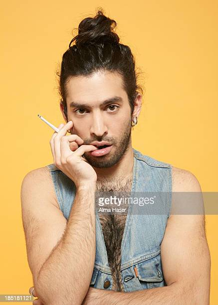 man with top-not and cigarette in feminine pose - homme poilu photos et images de collection