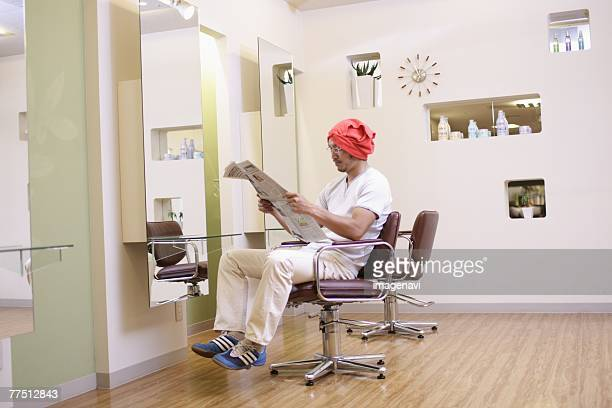 Man With Towel on Head Reading a Newspaper in Hair Salon
