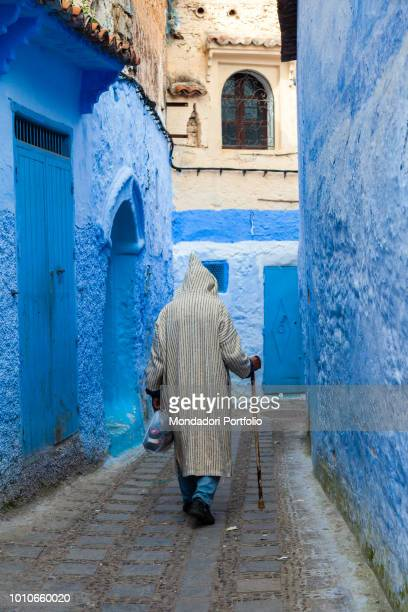 Man with traditional Moroccan dress and walking stick walks in an alley of Chefchaouen April 2018