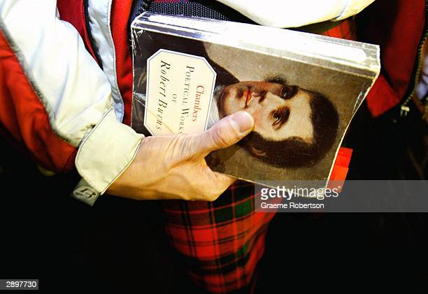 Man with traditional Scottish tartan holds a book with Robert Burns face on it at Burns Night January 24 2004 in London England Scots across the...