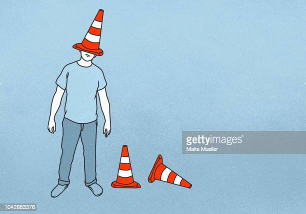 man with traffic cone on head - dunce's hat stock pictures, royalty-free photos & images