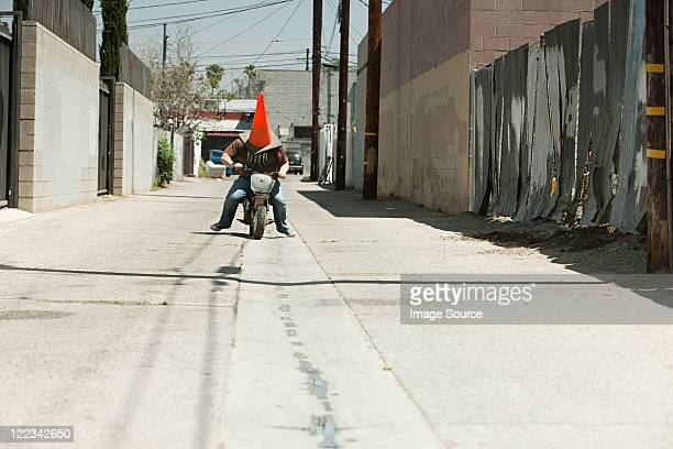 man with traffic cone on head, riding motorbike - traffic cone stock pictures, royalty-free photos & images