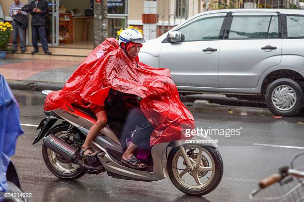 Man with two kids on a motorbike in rain