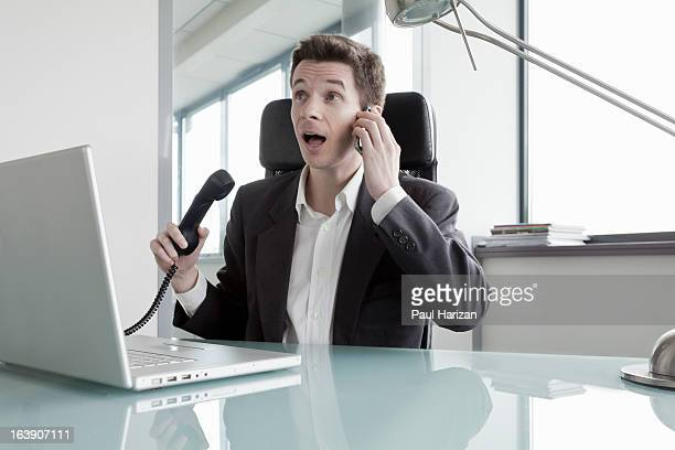 man with two phones in the office