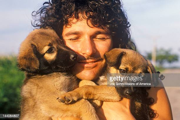 Man with two puppies IN