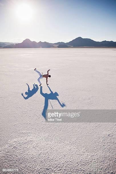 Man with two shadows performing capoeira on Bonneville Salt Flats, Utah, USA