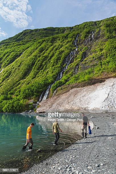 Man with two teenage boys on the beach in front of green mountain with waterfall at Shoup Bay State Marine Park, Prince William Sound