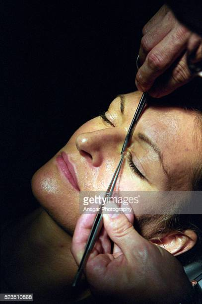 man with two tweezers at a eye of a young woman - stiches stock photos and pictures