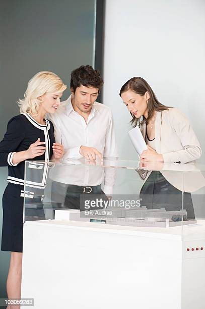 Man with two women looking at an architectural model
