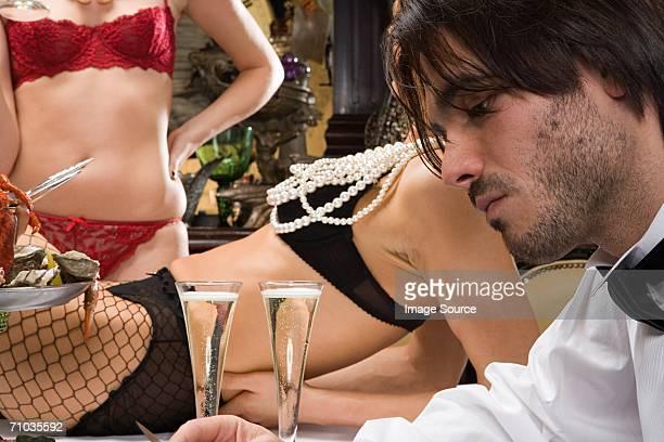 Man with two women wearing underwear in banquet hall