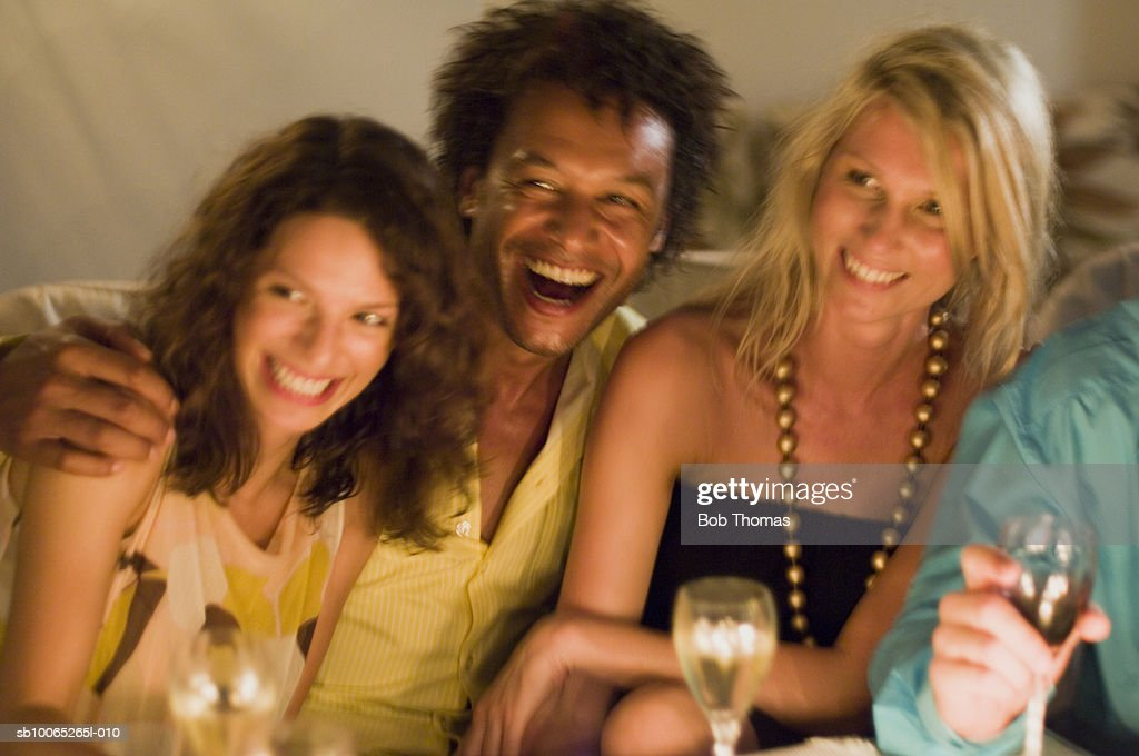 Man with two young women, looking away, laughing : Foto stock