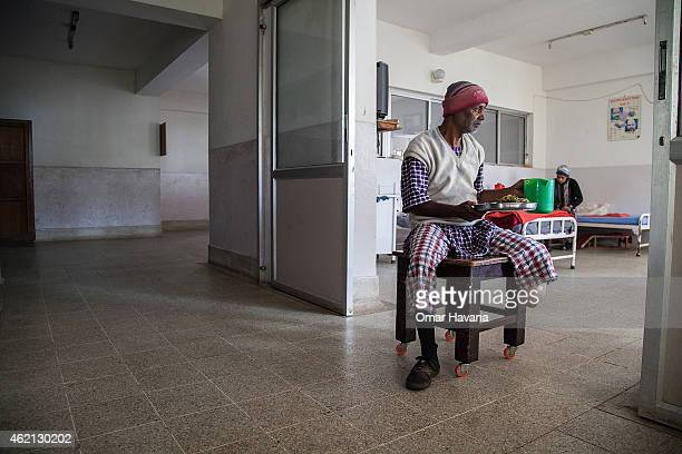 A man with ulcers on his feet moves around using a table with wheels attached while carrying his lunch inside Leprosy Mission Nepal's Anandaban...