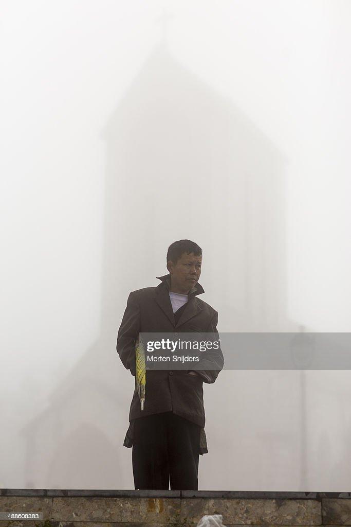Man with umbrella at misty church : Stockfoto