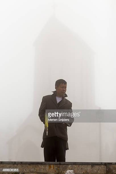 man with umbrella at misty church - merten snijders stock-fotos und bilder