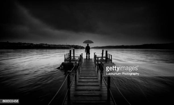 Man With umbrella at the pier