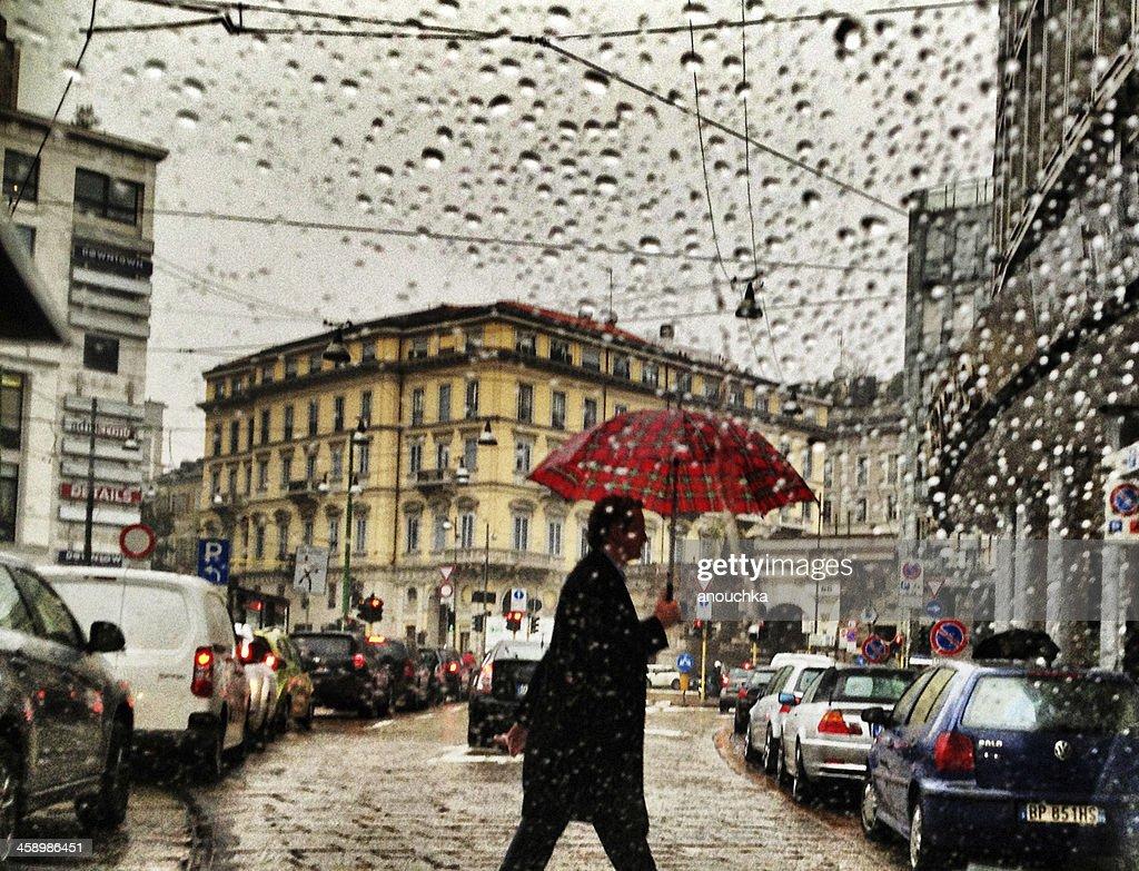 Uomo con ombrello sotto la pioggia strada di attraversamento di Milano, Italia : Foto stock