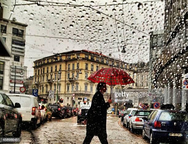 Uomo con ombrello sotto la pioggia strada di attraversamento di Milano, Italia