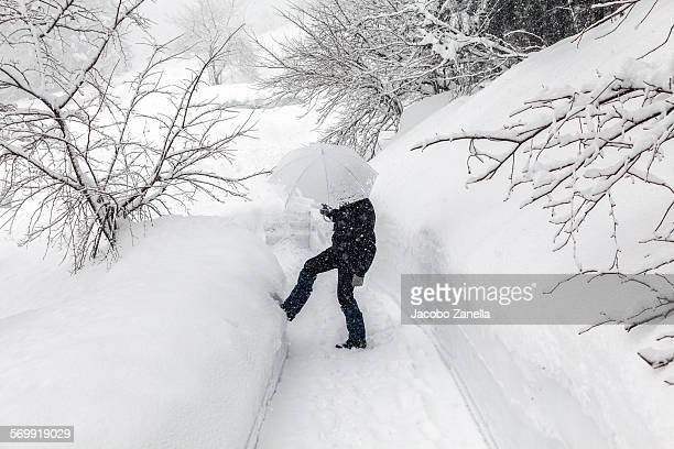 Man with umbrella in a snow road