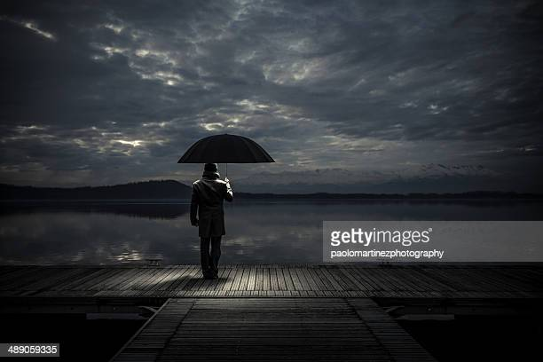 Man with umbrella standing on pier