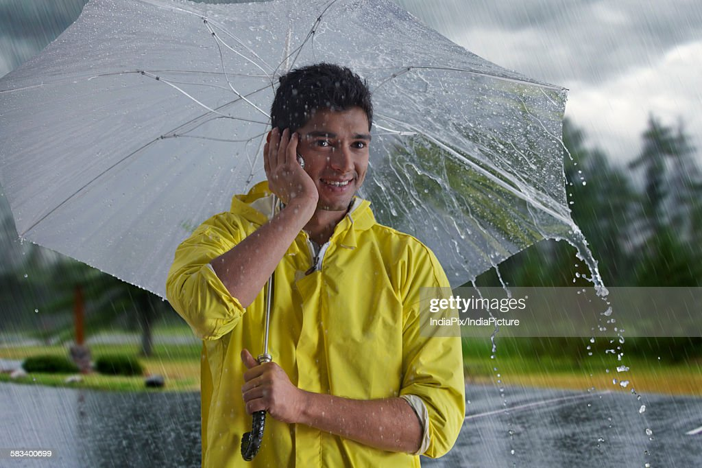 Man with umbrella talking on mobile phone : Stock Photo