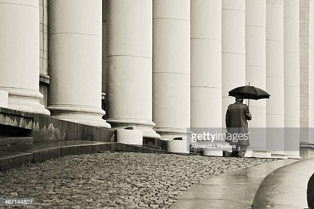man with umbrella walking away past columns - alexandra pavlova stock pictures, royalty-free photos & images