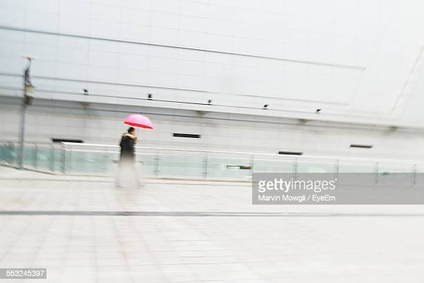 Man With Umbrella Walking By Building