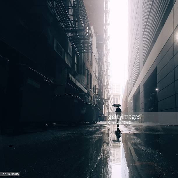 Man With Umbrella Walking Down City Street